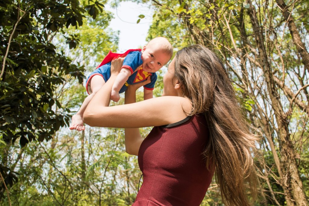 Women holding super baby in air after graduating from NICU